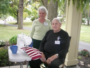 Edith and Charles Dyke, with the beginnings of his next American flag quilt, on the porch of the High Street Manor Bed and Breakfast.