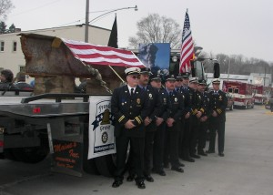 Urbana firefighters and paramedics stand in front of the World Trade Center steel on Saturday.